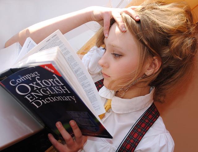 dívka koukající do slovníku